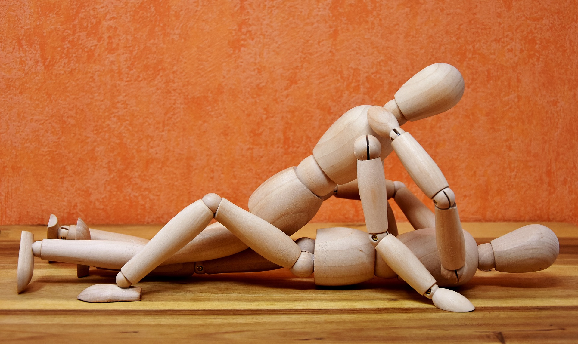 Two gender neutral wooden figures in a sexual position.